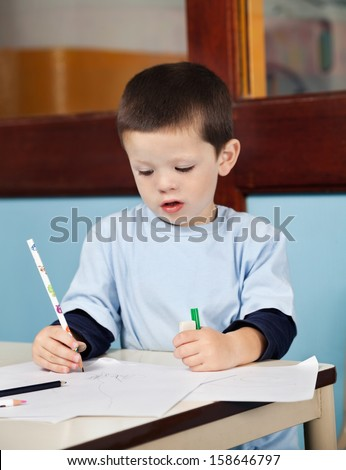 Cute little boy with pencil drawing on paper in classroom - stock photo
