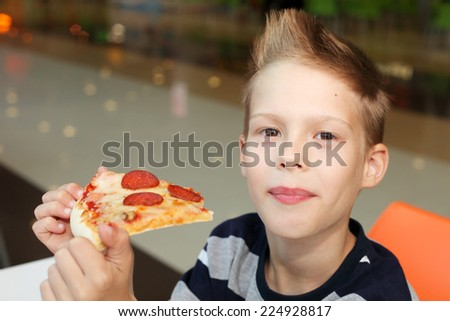 cute little boy with pizza - stock photo