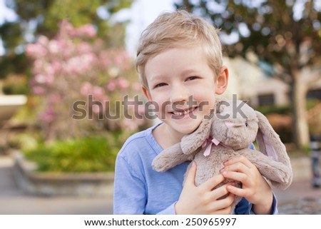 cute little boy with plush bunny toy at easter and spring time with blooming magnolia in the background - stock photo