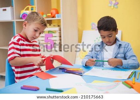 Cute little boys drawing at desk at the nursery school - stock photo