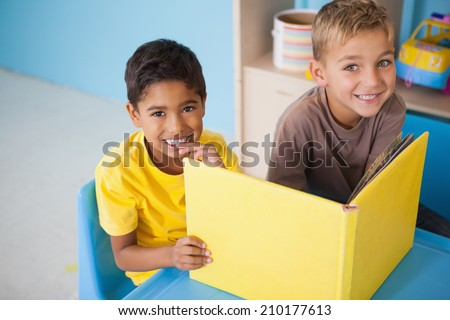 Cute little boys reading at desk in classroom at the nursery school - stock photo