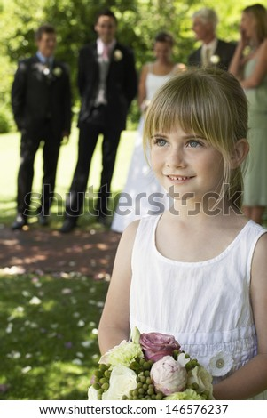 Cute little bridesmaid holding bouquet in lawn with guests and wedding couple in background - stock photo