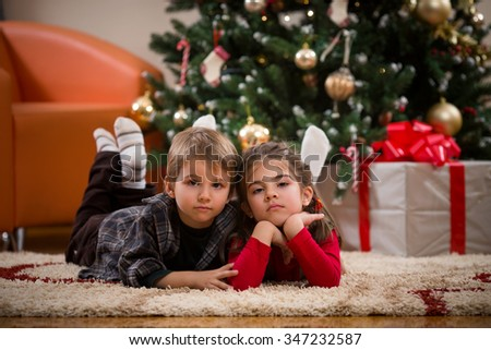 Cute little brother and sister lying on the floor in front of the Christmas tree - stock photo