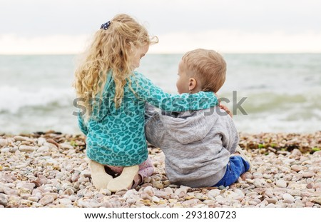 cute little brother and sister playing on the beach  - stock photo