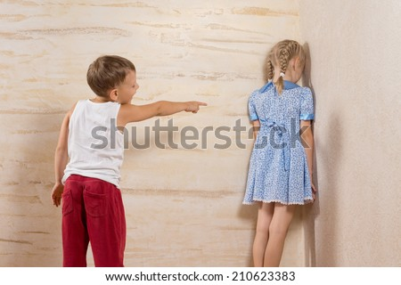 Cute Little Brother Laughing To His Sister Facing on Wooden Walls - stock photo