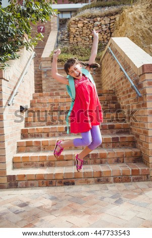 Cute little brunette child jumping with arms stretched - stock photo