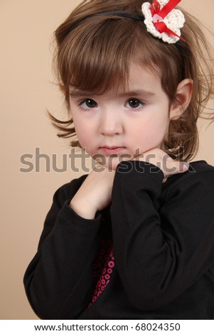 Cute little brunette toddler with serious expression - stock photo