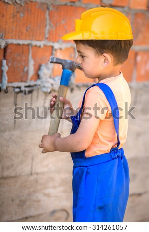 cute little builder in hardhats with hammer working outdoors - stock photo