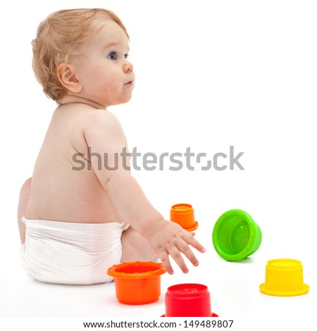 Cute little caucasian boy 11 months old sits and plays with toys on white background - stock photo