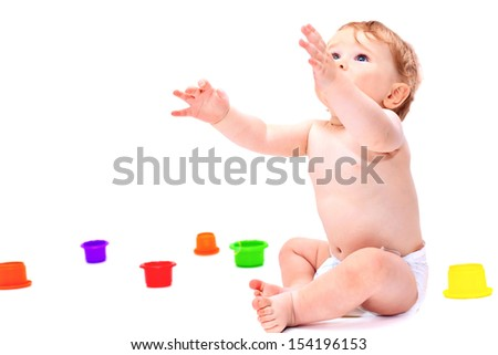 Cute little caucasian boy 11 months old sits surrounded with toys holding hands up on white background - stock photo