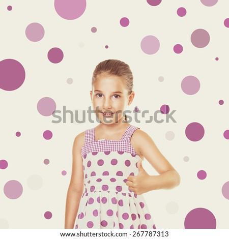 Cute little Caucasian girl in white dress with purple dots gesturing thumbs up. Square format image, retouched, filter applied, beige background with random purple dots.  - stock photo