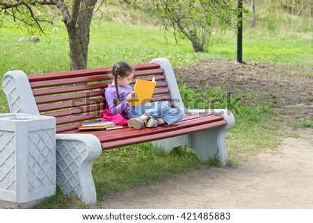 Cute little caucasian girl reading book sitting on a bench in spring park - stock photo