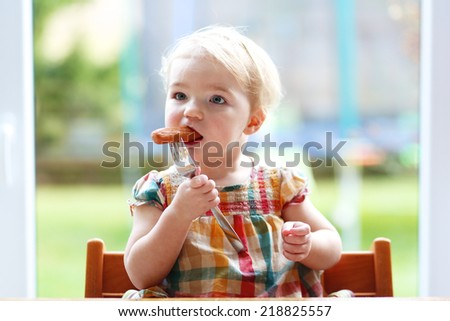 Cute little child, blonde toddler girl biting on sausage from metal fork sitting on high feeding chair in the kitchen nearby big window with garden view - stock photo