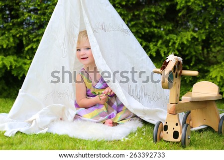 Cute little child, blonde toddler girl wearing beautiful dress enjoying summertime playing outdoors in the garden hiding in home-made tent on a sunny day - stock photo