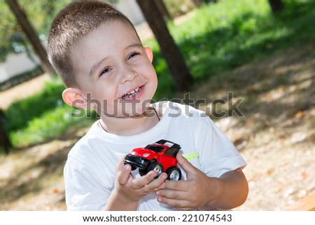 Cute little child boy plays with toy car in park on nature at summer. Use it for baby, parenting or love concept - stock photo