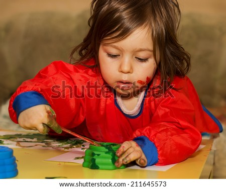 Cute little child drawing and studying at daycare - stock photo