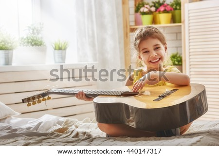 Cute little child girl playing guitar. - stock photo