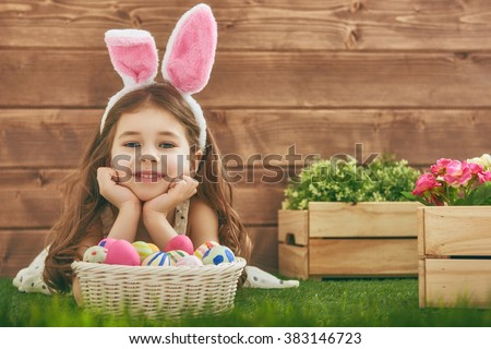Cute little child girl wearing bunny ears on Easter day. Girl hunts for Easter eggs on the lawn near the house. Girl holding basket with painted eggs. - stock photo