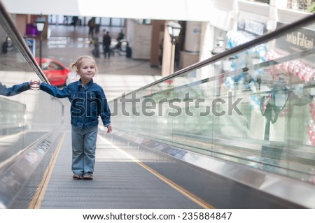 Cute little child in shopping center standing on moving staircase, escalator - stock photo