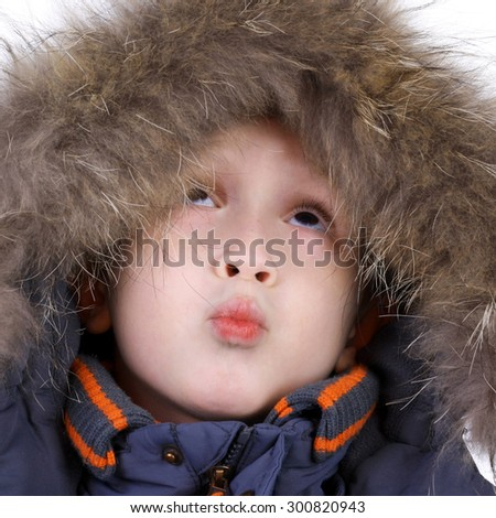 cute little child in the winter fur clothing looking up - stock photo
