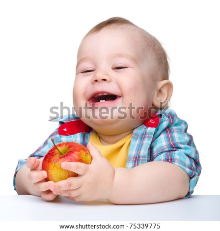 Cute little child is eating red apple and smile while sitting at table, isolated over white - stock photo