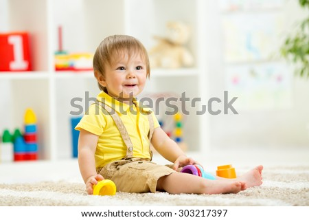 Cute little child is playing with toys while sitting on floor in room - stock photo