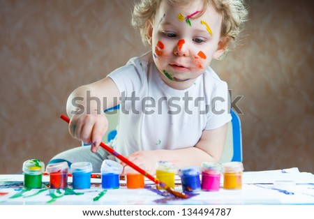 Cute little child painting with paintbrush and colorful paints - stock photo