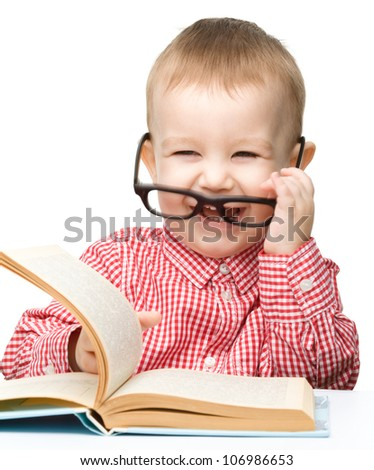 Cute little child play with book while sitting at table and wearing glasses, isolated over white - stock photo
