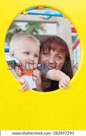 cute little child playing with his mother on the playground outdoors - stock photo