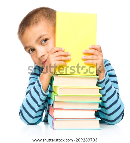 Cute little child plays with book while sitting at table, isolated over white - stock photo