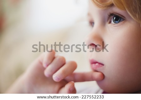 Cute little child thinking, close up, soft focus photo  - stock photo