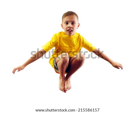 Cute little elementary boy exercising and jumping. Isolated over white background. - stock photo