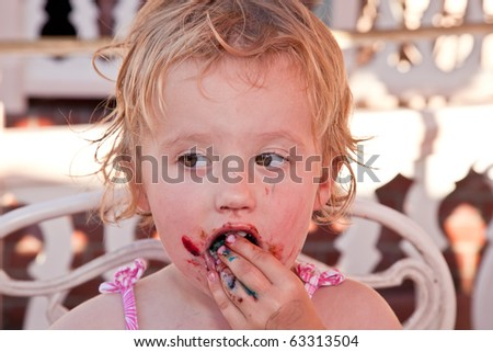Cute little European toddler girl enjoying a piece of chocolate cake. - stock photo