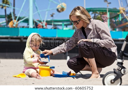 Cute little European toddler girl having fun with sand on the beach. - stock photo