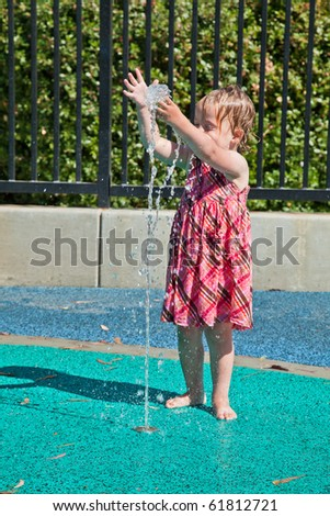 Cute little European toddler girl having fun with water at the playground in park - stock photo