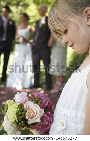 Cute little flower girl holding bouquet with guests and wedding couple in background - stock photo