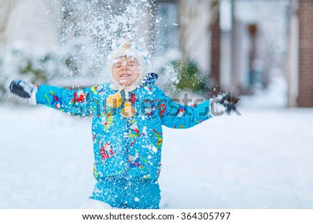 Cute little funny boy in colorful winter clothes catching snow and snowflakes, outdoors during snowfall. Active outdoors leisure with children in winter. Kid with warm hat, hand gloves, winter fashion - stock photo