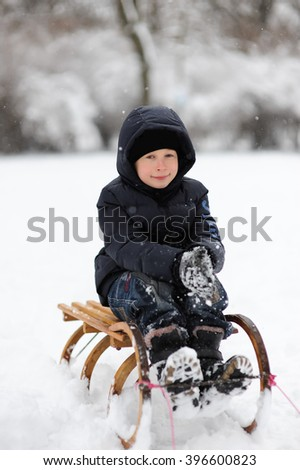 Cute little funny boy sledding, having fun on snow in winter, outdoors during snowfall. Active outdoors leisure with children in winter. Happy little kid is playing in snow, good winter weather. - stock photo