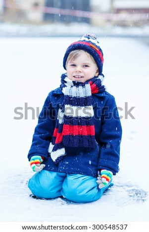 Cute little funny kid boy in colorful winter clothes sitting on snow, outdoors during snowfall on cold day. Active outdoors leisure with children in winter. - stock photo