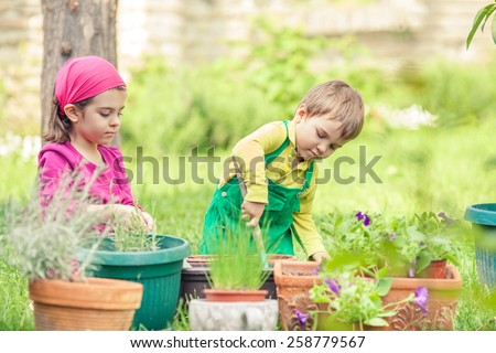 Cute little gardeners planting flowers in front or back yard - stock photo