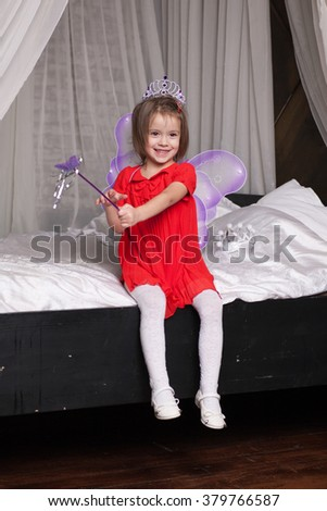 Cute little girl about four years old in fairy costume sits on the bed - stock photo