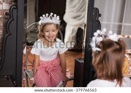 Cute little girl about four years old looking at herself in the mirror and smiling - stock photo