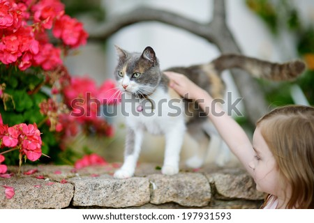 Cute little girl and a cat outdoors - stock photo