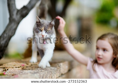 Cute little girl and a cat outdoors on hot summer day in Italy - stock photo