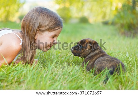 Cute little girl and dog puppy. Friendship and care concept - stock photo