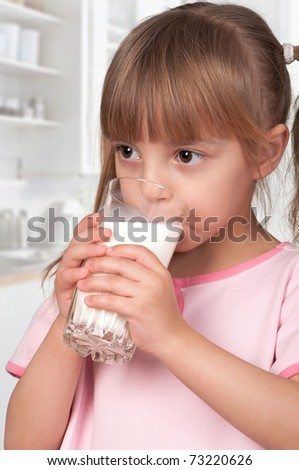 Cute little girl and glass of milk in kitchen - stock photo