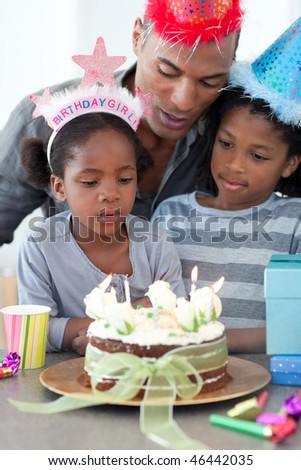 Cute little girl and her family celebrating her birthday in the kitchen - stock photo