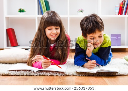 Cute little girl and little boy are doing their homework.Homework - stock photo