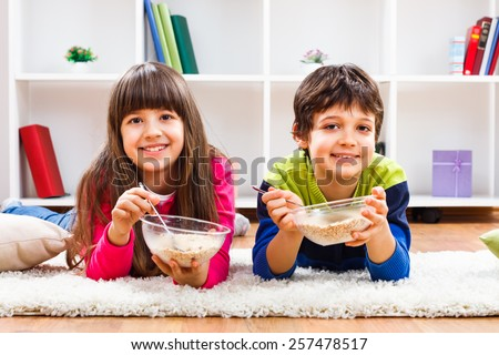Cute little girl and little boy are eating cereals.Healthy breakfast for children - stock photo