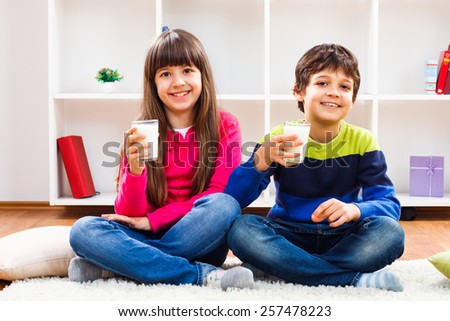 Cute little girl and little boy are holding glass of milk and looking at camera.We like to drink milk - stock photo